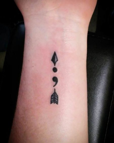 Arrow tattoo with semicolon on wrist